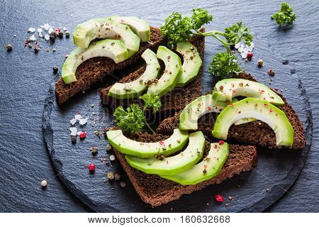 Sandwiches with rye bread fresh sliced avocado parsley and ground pepper on black stone.