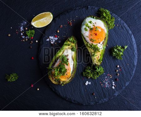 Avocado baked with eggs fresh parsley ground pepper. Black stone background top view.