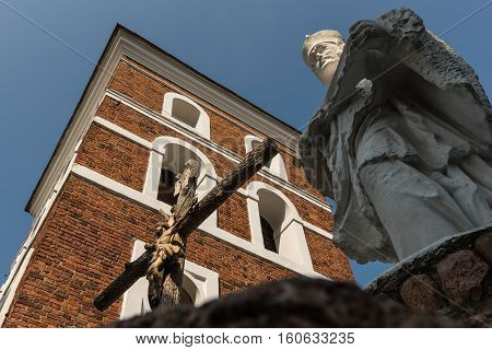 NESWIZH, BELARUS - SEPTEMBER 12.2016:  Crucifixion of Jesus Christ, and the sculpture of St.Yan the background of the bell tower of the Catholic Church in Nesvizh