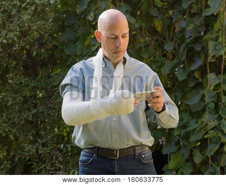 Young Man With An Arm Cast Texting On His Phone