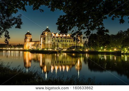 MIR, BELARUS - AUGUST 28.2016:  Illuminated medieval castle in the Belarusian town of Mir with night reflection in a lake with silhouettes of trees leaves