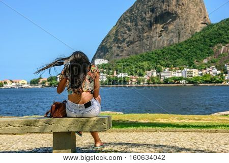 Beautiful woman with flying black hair and brown bag sitting on the bench on the background of Sugarloaf and Guanabara bay in Rio de Janeiro, Brazil