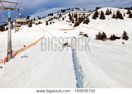 Ski chair lift moving, rope way in Alps mountains in Mayerhofen, Austria. Snowcat on ski slope