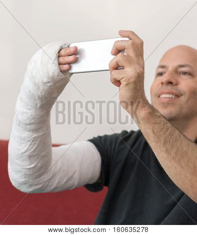 Young Man With An Arm Cast Taking A Selfie