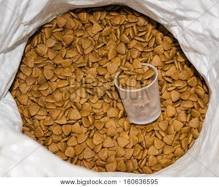 pet food in a bag with a measured glass closeup