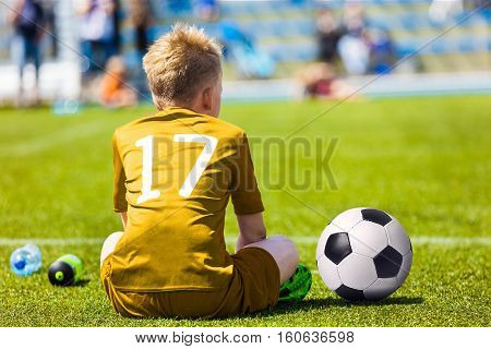 Young Soccer Football Player. Little Boy Sitting on Soccer Pitch. Youth Football Player in Yellow Soccer Jersey