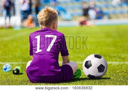 Young Soccer Football Player. Little Boy Sitting on Soccer Pitch. Youth Football Player in Purple Soccer Jersey