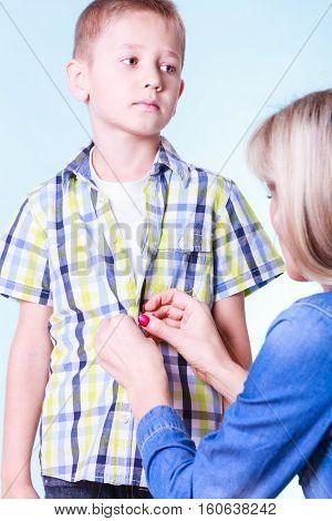 Mother Help Dress Son Fasten Buttons.