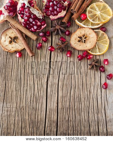 Dried citrus and garnet on a wooden background