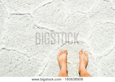 Naked human barefoot on salt surface background at tour excursion in Salar de Uyuni near Isla Incahuasi - Freedom and carefree wanderlust lifestyle concept traveling around world - Bright sunny filter