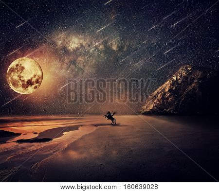 Young man riding a wild horse near the seaside in a starry night with a full moon and falling stars. New lands discovery adventure and friendship concept.