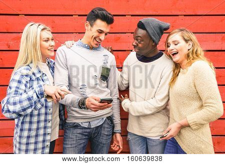Multiracial hipster best friends group having fun together with smartphone - Modern technology interaction concept with young people using mobile smart phone - Wifi internet connection spots outdoors