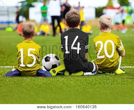 Children Soccer Team Playing Match. Football Game for Kids. Young Soccer Players Sitting on Pitch. Little Kids in Yellow and Black Soccer Jersey Sportswear