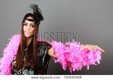 Retro flapper woman on carnival time. Young female pink plume black feather on head and sequin glossy evening dress