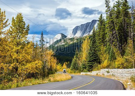 The road bends sharply in the woods. Perfect storm sunset over the Rocky Mountains. The concept of active tourism