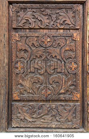Old wooden door with carved patterns. Architecture