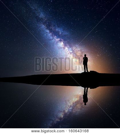 Night starry sky with Milky Way and silhouette of a standing man on the hill near the lake with sky reflection in water. Milky way and man. Galaxy and silhouette of a man. Universe. Travel background