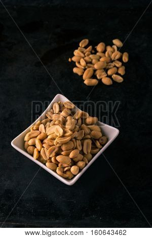 Dark Tray With Salted Peanuts On Heap And In White Bowl