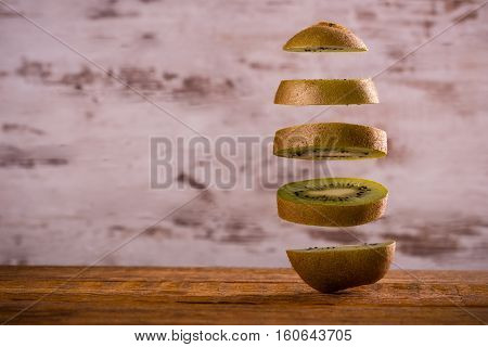 One Kiwi Fruit Cut To Slices Which Floating Over Each Other