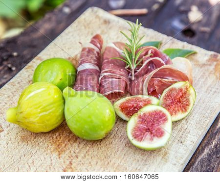 Ripe fig fruits and bacon or prosciutto. Food to accompany the drinks.