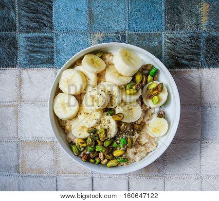 Breakfast: oatmeal with banana, nuts, hemp seeds and hemp milk. Top view, toning.