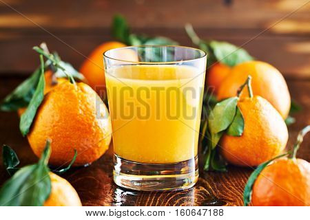 fresh glass of orange juice on rustic table top