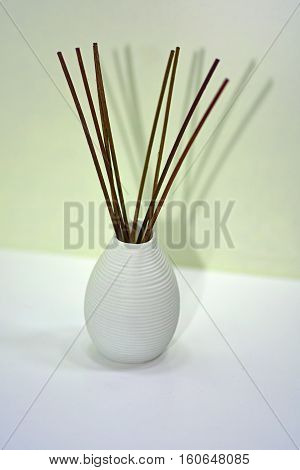 Aromatic sticks for home in white ceramic vase. Isolated on white