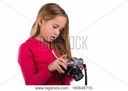 Young girl looking down on a vintage SLR camera isolated on a white background