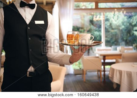 Waiter serving tea at restaurant, close up view