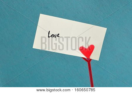 Valentines day. A note holder with a red heart with a note reading love isolated against a blue background