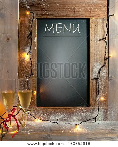 Champagne glasses next to menu board with space