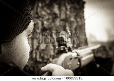 Hunter man with gun aiming and prepared to make a shot during hunting