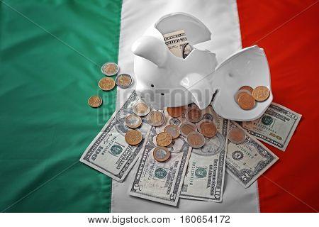 Broken piggy bank with money on flag