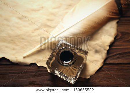 Feather pen with inkwell and blank paper on wooden table closeup