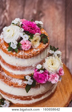 Closeup shot of a two layered homemade naked cake  decorated with flowers on wooden cut stand