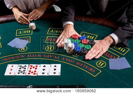 couple playing poker at the table. The blonde girl and a guy in a suit. close up hands. bets all-in