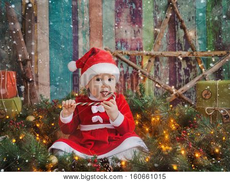 baby in Santa dress Christmas background eating candy