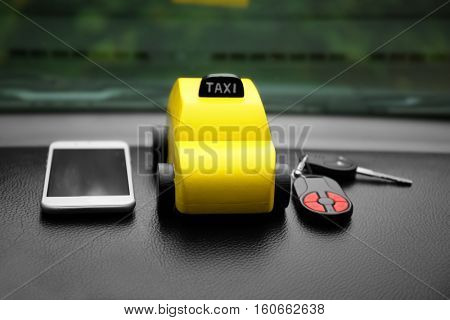 Yellow toy taxi with phone and key on car dashboard