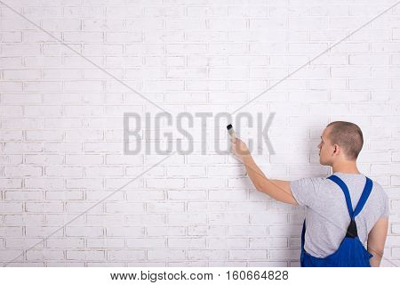 Back View Of Man Painter In Workwear Painting Brick Wall With Brush And Copy Space