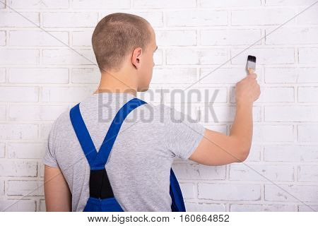 Back View Of Man Painter In Workwear Painting Brick Wall With Brush