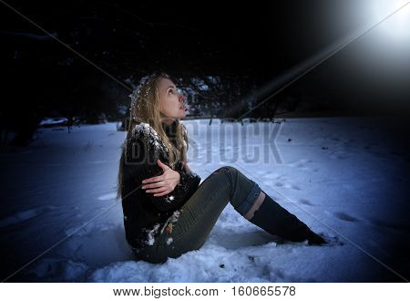 The young beautiful frozen woman sits in snow in the night park