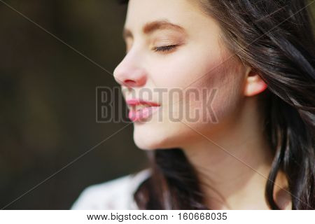 Portrait of a dreamy cute woman meditating outdoors with eyes closed with the effect of blur on a dark background closeup.