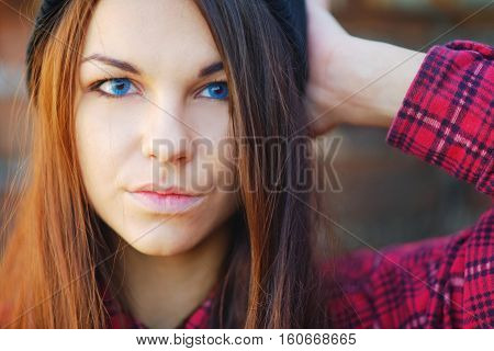Portrait of a serious beautiful long haired brunette girl with blue eyes outdoor closeup