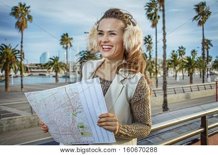 Woman On Embankment In Barcelona With Map Looking Into Distance