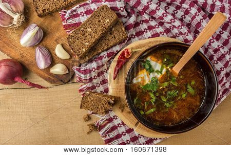 Tasty and nutritious borsch-soup with meat, potatoes, cabbage, tomatoes, beans, sour cream, parsley, onion, garlic, dark bread in a clay plate on a wooden tray and wooden table. Top view.