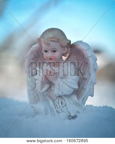 Guardian angel on blue sky background. Religion and faith concept. Winter time.