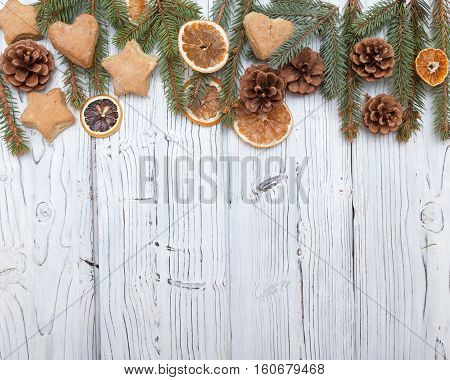 Christmas decoration frame on old grunge white wooden board with fur tree branches, cookies, pine cones. Flat lay with copy space.