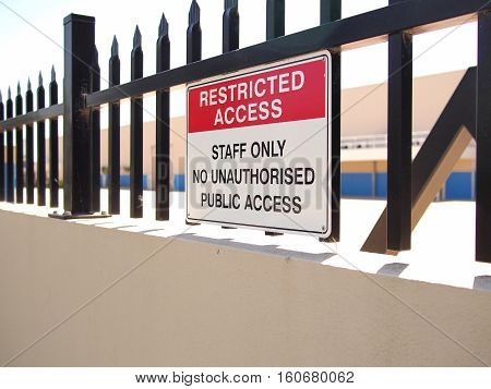 Access restricted sign on a steel fence tipped wall of an industrial estate Melbourne Australia 2016