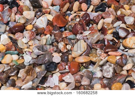Polished rocks consisting of jasper and agate in a pile for background or texture