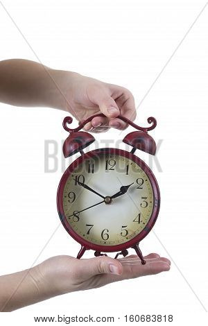 Female hands with the old red alarm clock